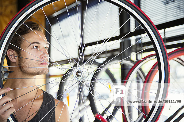 Young man examining spokes on wheel in bicycle shop