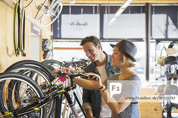 Couple looking at price tags on bicycles in bicycle shop