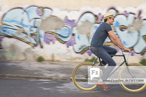 Hipster-Mann beim Radfahren auf der Straße entlang der städtischen Graffiti-Wand