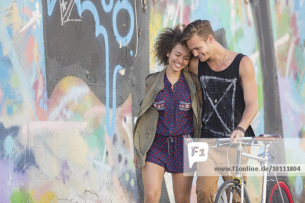 Couple hugging and walking with bicycle along urban graffiti wall