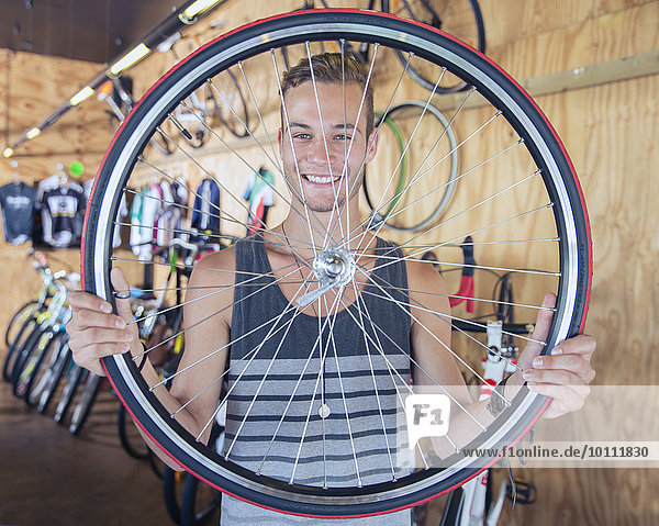 Portrait smiling young man holding bicycle wheel in bicycle shop