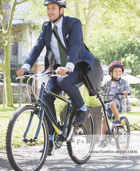 Geschäftsmann in Anzug und Helm auf Tandemfahrrad mit Sohn