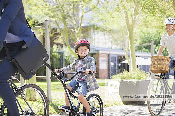 Portrait lächelnder Junge im Helm auf Tandemfahrrad mit Vater im Park