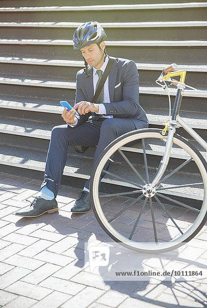 Geschäftsmann im Anzug und Helm SMS mit Handy neben dem Fahrrad auf der sonnigen Stadttreppe
