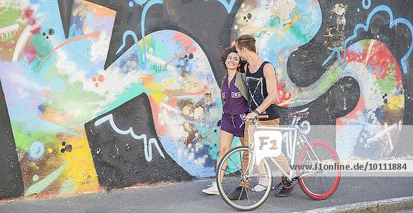 Junges Paar mit Fahrradumarmung und Spaziergang entlang der urbanen bunten Graffiti-Wand