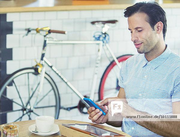 Mann SMS mit Handy in der Nähe des Fahrrads im Cafe