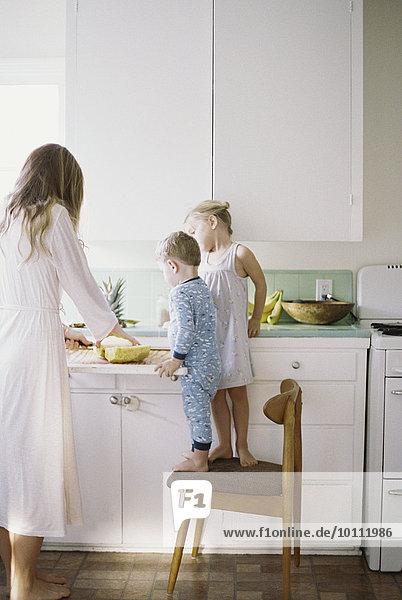 stehend Frau Frische schneiden Küche Ananas