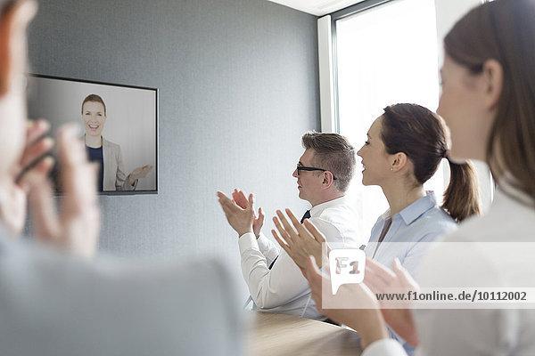 Geschäftsleute klatschen für Geschäftsfrau auf Videokonferenz-Bildschirm