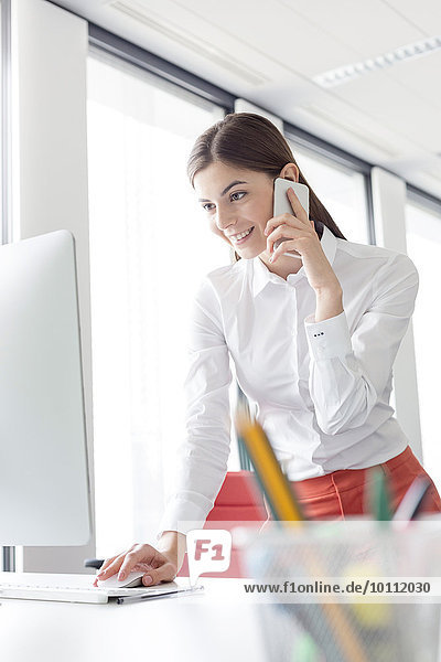 Businesswoman talking on cell phone working at computer in office