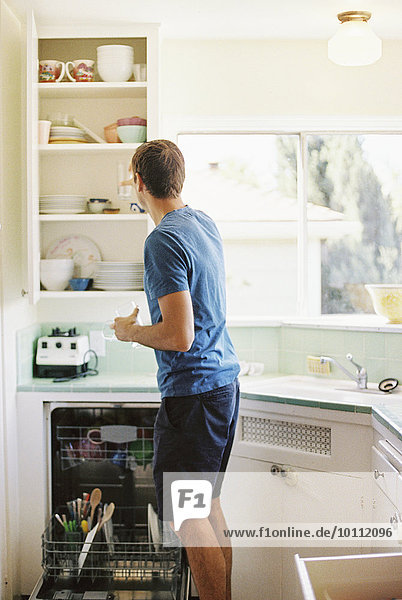 stehend Mann Essgeschirr Küche frontal Schrank Rückansicht Ansicht
