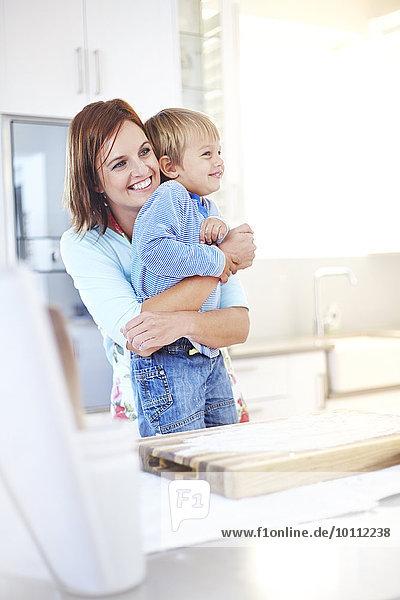 Lächelnde Mutter umarmt Sohn in der Küche