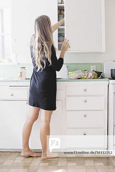 A woman with long blond hair standing barefoot in a kitchen  opening a cupboard.