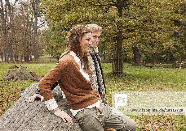 Paar lehnt in Waldlichtung an gefälltem Baum