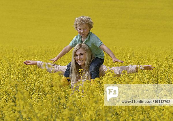 Mutter mit Sohn in Rapsfeld