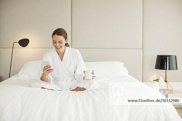 Handy Frau Kurznachricht lächeln Bett Bademantel trinken Kaffee