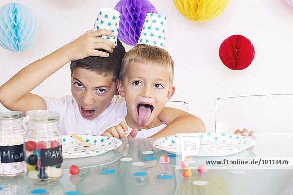 Junge Brüder machen Gesichter während einer Geburtstagsfeier Junge Brüder machen Gesichter während einer Geburtstagsfeier