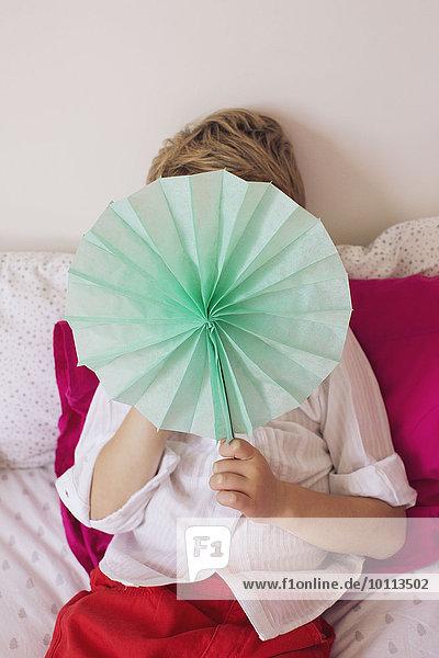 Little boy hiding behind tissue paper flower