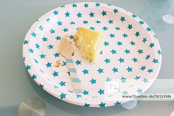 Teilweise gegessenes Kuchenstück auf festlichem Pappteller