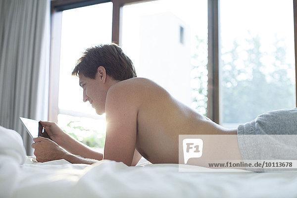 Mann im Bett liegend mit digitalem Tablett