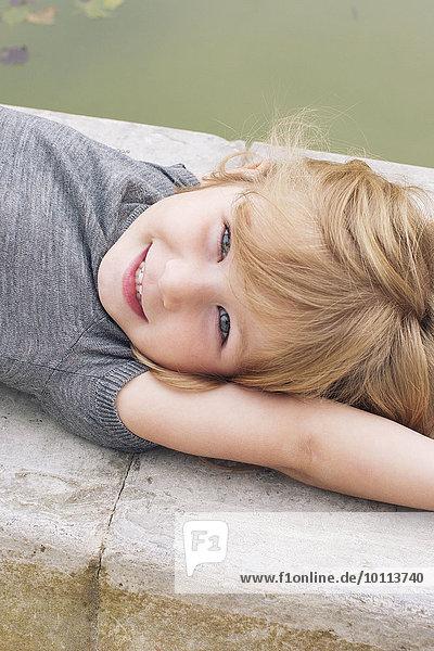 Kleines Mädchen am Teich liegend  Portrait