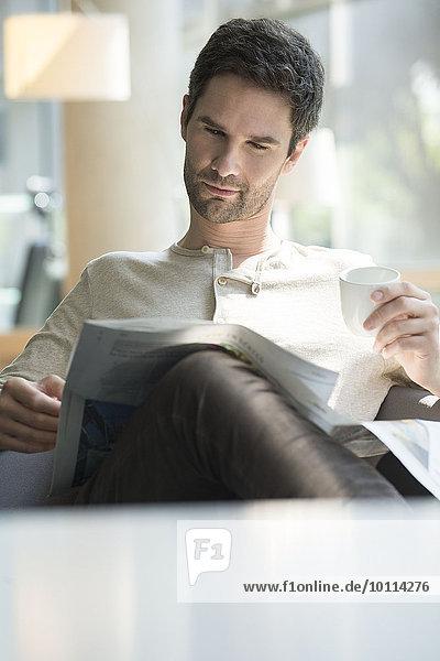 Mann liest Zeitung und trinkt Kaffee