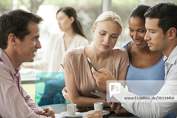 Kollegen  die während der Kaffeepause auf das Smartphone schauen