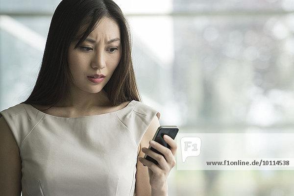 Frau erhält schlechte Nachrichten auf dem Smartphone