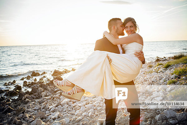 tragen Braut Bräutigam Strand Sonnenuntergang Kieselstein
