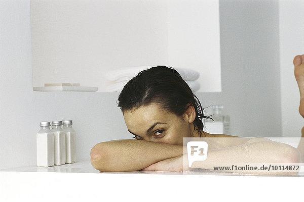 Frau in der Badewanne  Kopf auf den Armen ruhend  Blick in die Kamera
