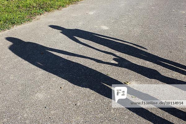 Schatten einer Familie  die im Freien Händchen hält.