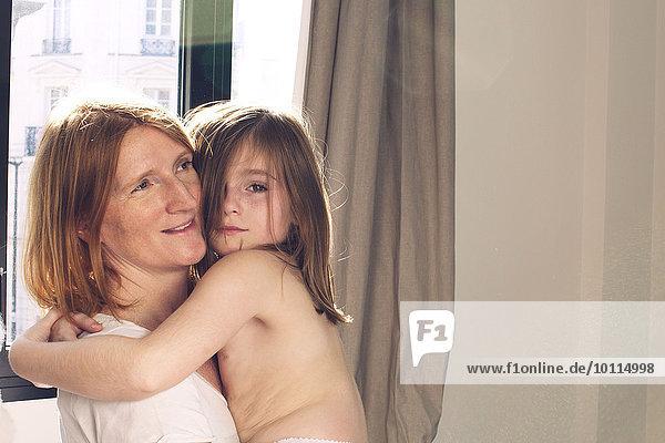 Kleines Mädchen umarmt seine Mutter
