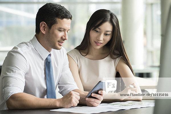 Kollegen  die gemeinsam im Büro auf das Smartphone schauen