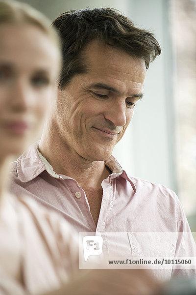 Ein Mann  der in Gedanken herabblickt und lächelt.