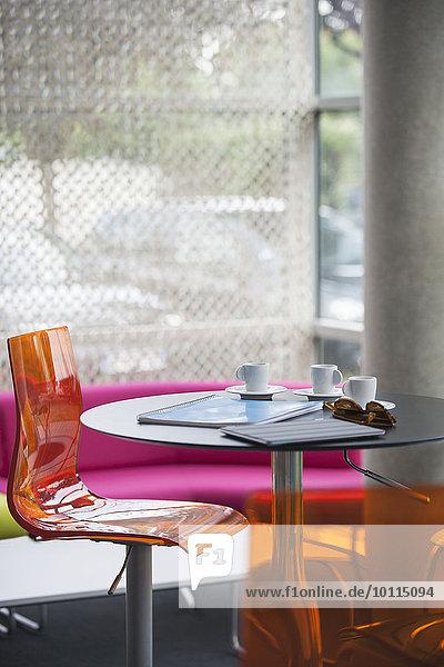 Kaffeetassen  Notizbücher und Sonnenbrille auf dem Tisch im Café stehen gelassen