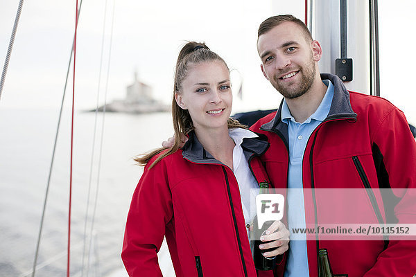 Young couple drinking beer on sailboat  Adriatic Sea