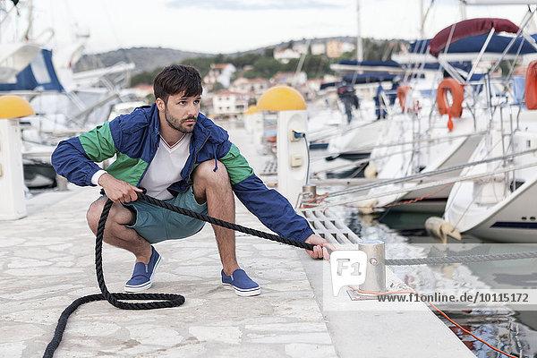 Mann Seil Tau Strick Kai befestigen Adriatisches Meer Adria