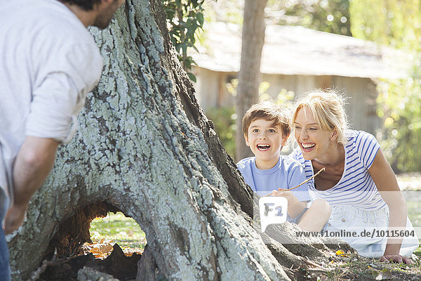 Young boy and mother hiding behind tree  playing hide-and-seek