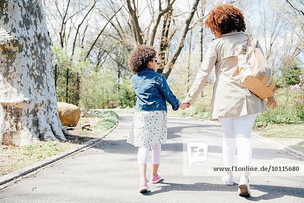 Full length rear view of mother and daughter walking holding hands