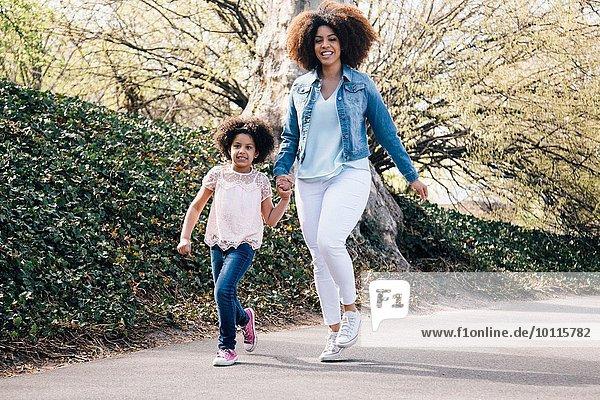 Ganzkörperaufnahme von Mutter und Tochter mit lächelnden Händen entlang des Weges