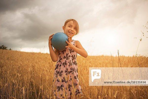 Mädchen mit blauer Kugel im Weizenfeld