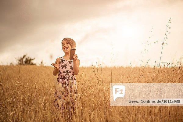 Mädchen mit Smartphone beim Lachen im Weizenfeld