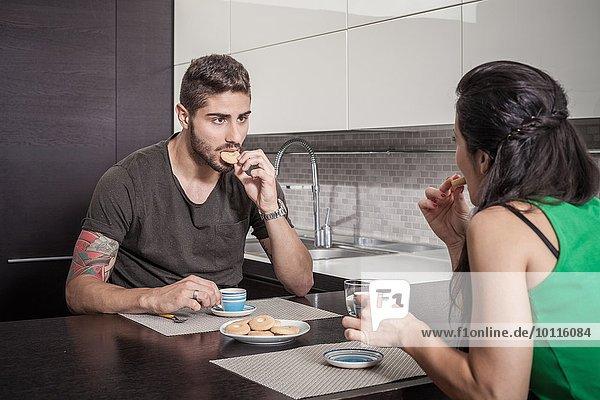 Junges Paar trinkt Kaffee und isst Kekse an der Frühstückstheke