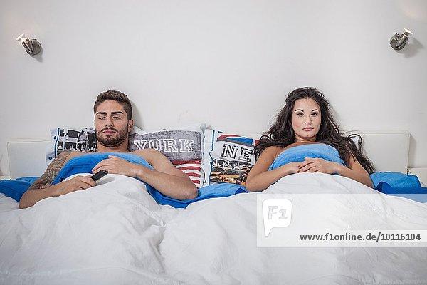 Junges Paar im Bett liegend schmollend