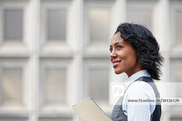 Portrait of young business woman holding paper work  looking away  smiling  side view