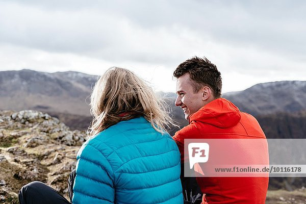 Young couple sitting on hilltop  rear view  Keswick  Lake District  Cumbria  United Kingdom