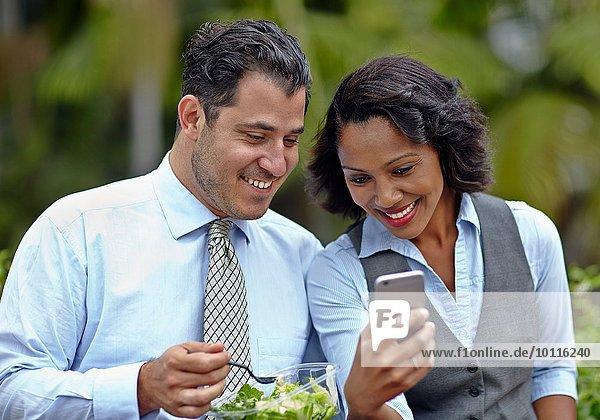 Geschäftsleute sitzen Seite an Seite und genießen einen Salat in der Mittagspause  schauen auf das Smartphone  lächeln
