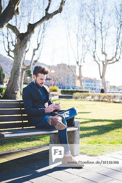 Junger Mann sitzt auf der Parkbank und liest Smartphone-Texte.
