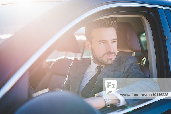 Junger Geschäftsmann  der aus dem Autofenster blickt