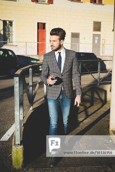 Stilvoller junger Mann mit Smartphone auf dem Gehweg