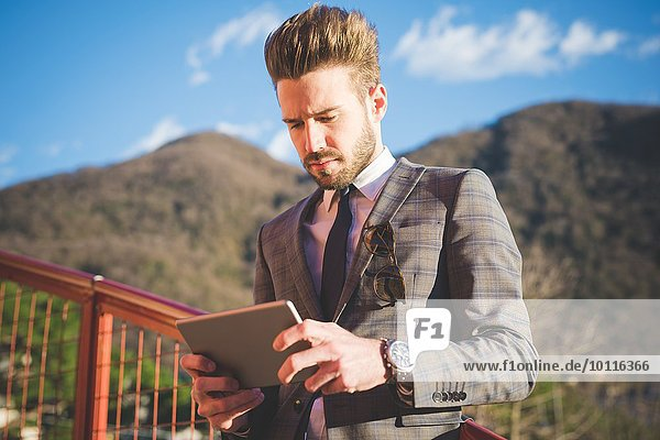 Junger Mann auf Fußgängerbrücke liest digitales Tablett  Rovato  Brescia  Italien